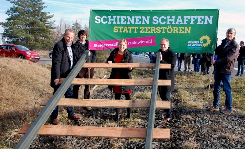 Die Grünen setzen das abgebaute Stück Gleis der Steigerwaldbahn symbolisch wieder ein.